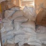 L'aide alimentaire Internationale : du riz et des sardines à l'huile, stockés au milieu des réserves de l'école (cahiers, stylos...).