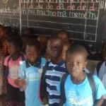 Les élèves de maternelle devant leur tableau, dans la classe.