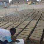 Les enfants et Babacar fabriquent les briques (en fait ce sont des parpaings).